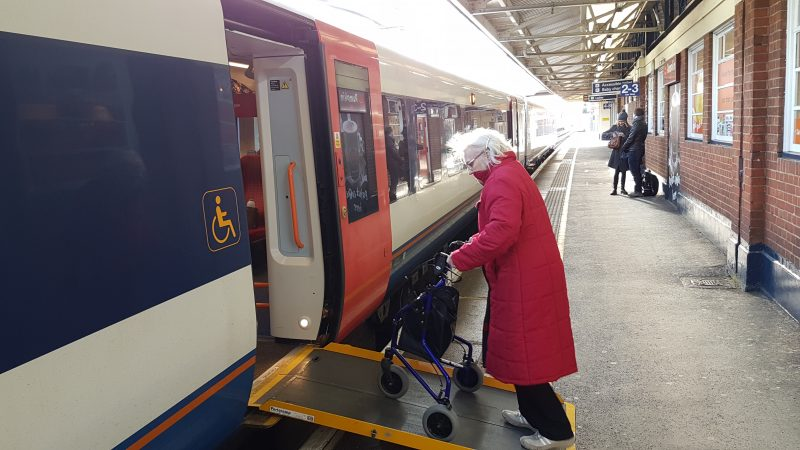 My mother boarding a train at Woking station, using a ramp and her rollator.