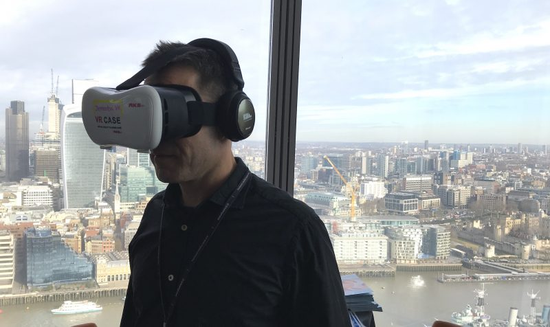 A man using a VR headset at an event with London city behind