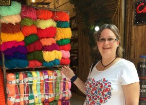 A woman looking at the camera and smiling with a t-shirt with a colourful heart design on. She is next to a stand of coloured threads. Strong colours are arranged at the top and pastels lower.
