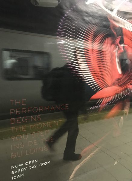A tube station in London reflected through an advertisement. The advertising is a poster with a red and white swirl. There is a man with a backpack reflected next to the swirl