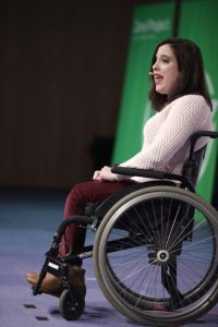 An image of Anastasia Somosa on stage speaking at the Zero Project Conference 2019. She is seated in her wheelchair wearing a soft pink knitted jumper and rich maroon trousers. Behind her is the Zero Project banner in green