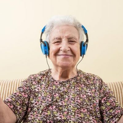 granny listening to music through headphones