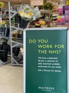 "A green street level sign outside a Waitrose store that says ""Do you work for teh NHS? We have a dedicated"