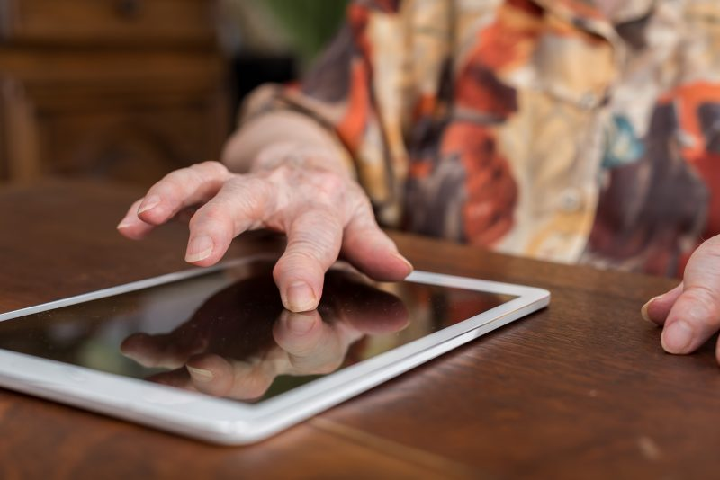 An old woman's hand on tablet