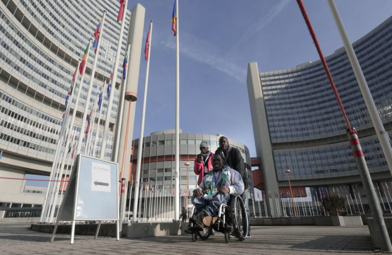 An outside photo at the UN in Vienna with three people, all of African origin following the sign to the Zero Project Conference. One is a wheelchair user